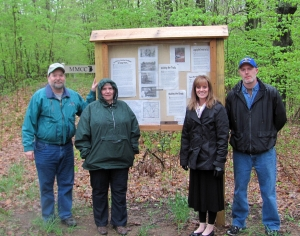 Coming out on a rainy May morning to take part in the dedication of the kiosk were (l-r) Joe Bradley, Carron Nevill, Cindy Mussell and Andy Coulson. Cindy is with the Mid-Michigan College Foundation and the others are part of the Clare County Historical Society.